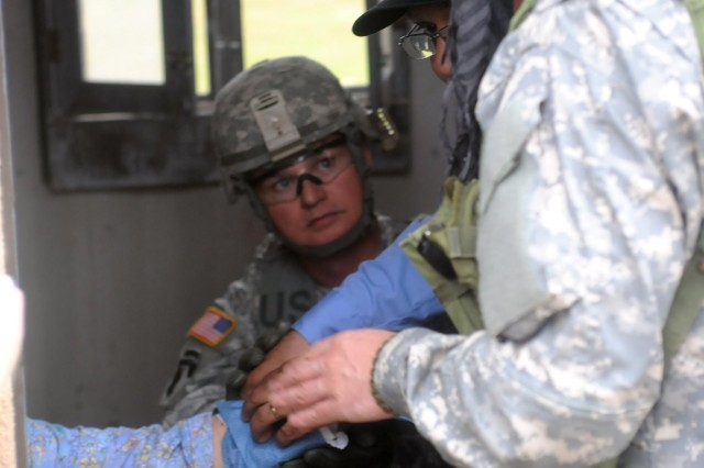 Patriot SFAB chaplain sits and tries to calm a woman as she has her fictional wound tended to by the medic at the Joint Readiness Training Center, March 23.