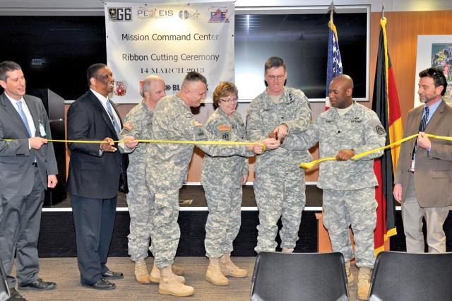 Col. John K. Arnold, with scissors, USAREUR deputy G6, and fellow military and civilian leaders mark the completion of the project to equip the Gen. John Shalikashvili Mission Command Center.