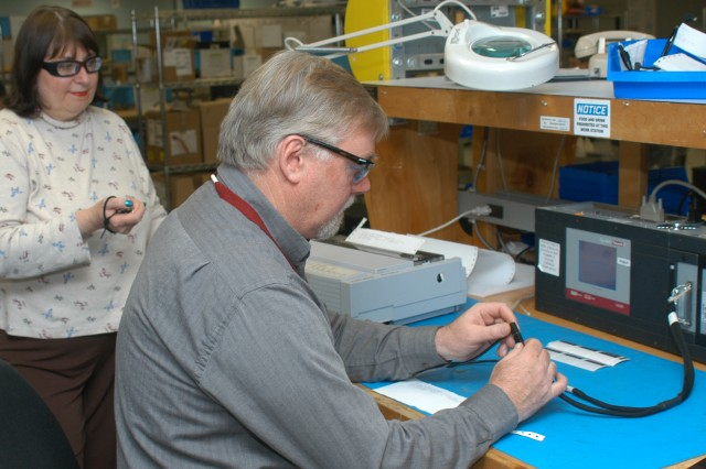 Nancy Jinselli times Electronics Mechanic Gene Pidich as he tests a cable to prove that a testing process improvement works at Tobyhanna Army Depot.  Jinselli recently led a team that improved the express mail process, earning a Lean Black Belt and cutting $1 million per year in costs.