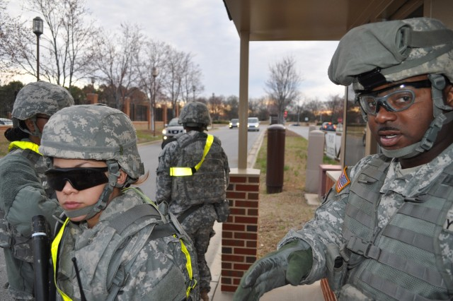 Spc. Alexander Ealy, a Memphis, Tenn., native, and squad leader assigned to the 11th Quartermaster Company, briefs his soldiers about security measures outside Womack Army Medical Center during a mass casualty exercise March 20.
