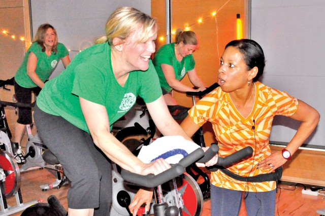 Spin class instructor Leslie Suddeth encourages Janneil Crader, a member of the Wiesbaden Protestant Women of the Chapel, during a class at the Wiesbaden Fitness Center.