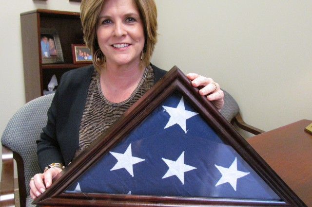 Teresa Schmitt holds the encased U.S. flag that was given to her mother when her father, Air Force Tech. Sgt. Elbert Austin Phillips, was killed during the Vietnam War. He is one of two missing-in-action Vietnam veterans whose names are engraved on the wall of the Huntsville/Madison County Veterans Memorial.