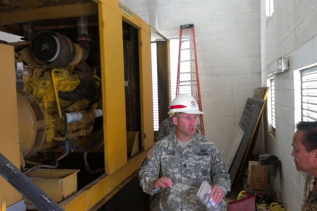 Sgt. 1st Class Brian George, Soldier with 249th Engineer Battalion (Prime Power), explains possible solutions to a generator issue at the Department of Public Health and Social Services facility.