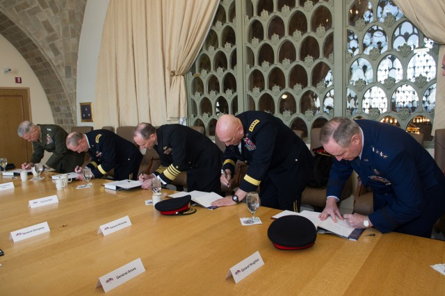 "Members of the U.S., U.K. Chiefs Committee sign the ""Council of War, The History of the Joint Chiefs of Staff"", during a historical meeting at the National War College at Fort McNair in Washington, D.C., March 27, 2013."