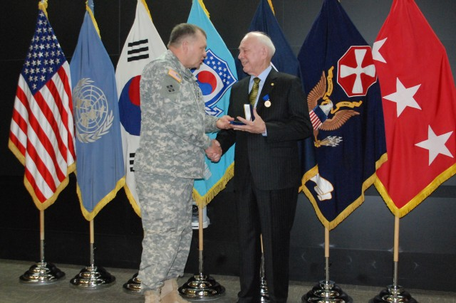 U.S. Army General James D. Thurman, commanding general of United Nations Command, Combined Forces Command and United States Forces Korea, left, presents a command coin to Joseph Shepard, right, during Shepard's federal service retirement ceremony, March 28, at U.S. Army Garrison Yongsan, Seoul, Korea. (Photo by Nikki Maxwell)