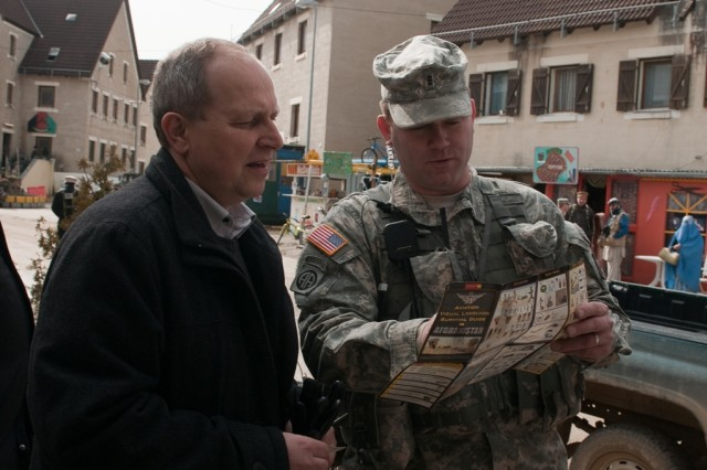 Chief Warrant Officer 3 John Clark, with the Mustang Observer Coach Trainer Team, Joint Multinational Readiness Center, shows a communication card for deployed Soldiers to Alfred Meier, the first mayor of Lupburg, during a tour of Joint Multinational Readiness Center, March 20, 2013.