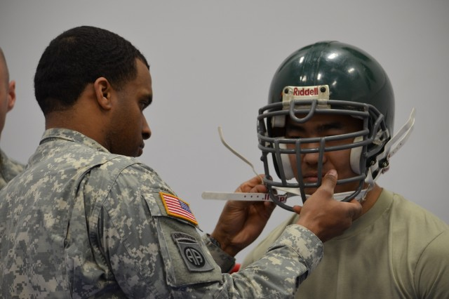 Staff. Sgt. Darnell Washington adjusts the head gear of Spc. Timothy Thompson prior to the start of a combative training exercise, March 20, 2013, at Arvin Gym at the U.S. Military Academy at West Point, N.Y.  Both Soldiers are assigned to Keller Army Community Hospital.
