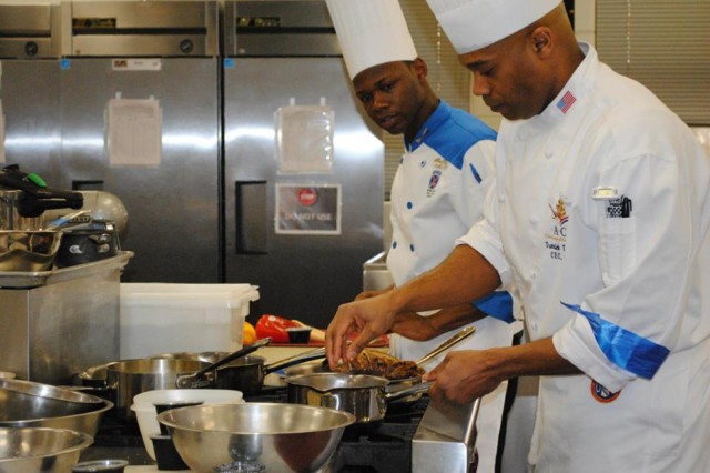 Spc. Christopher McClinton observes one of the staff cooks from Fort Lee's Culinary Arts School to see any trade secrets he might need for this year's competition.