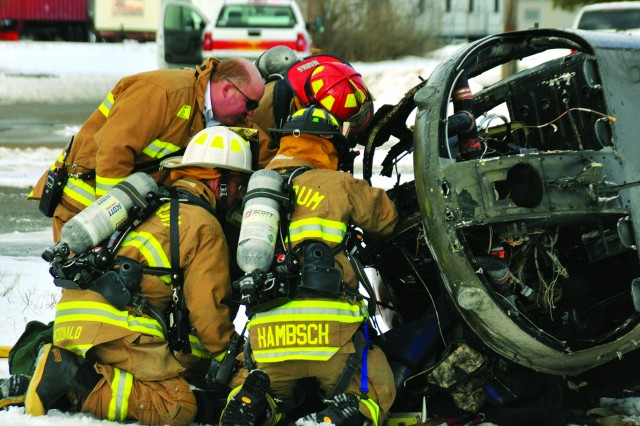 George Massarotti, Fort Drum assistant fire chief of training, instructs his crew in proper extricating techniques during an emergency response exercise Tuesday simulating an OH-58D Kiowa helicopter crash on post.