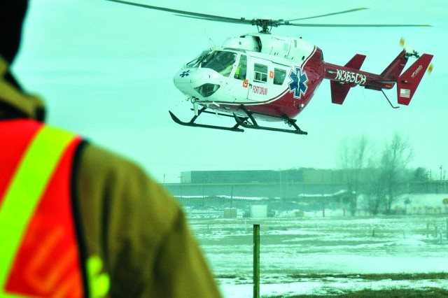 A Fort Drum firefighter awaits the landing of a helicopter operated by LifeNet, part of a national air medical transport company that opened a hub in Watertown last summer.