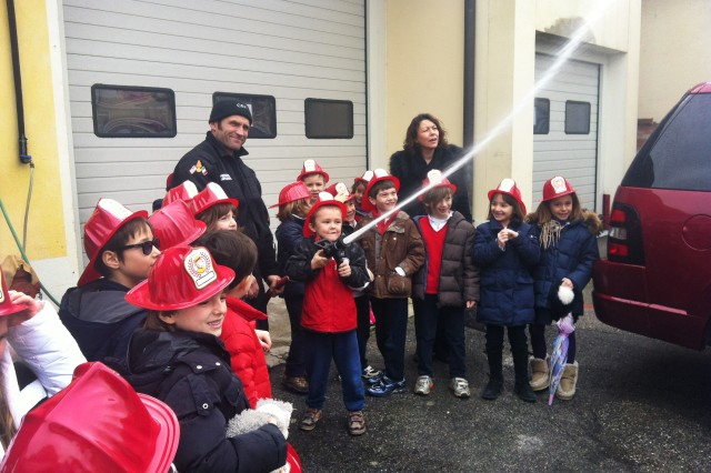 Children from Little English School in Vicenza, Italy, get their hands on the fire hose during a March 14, 2013, visit to the Caserma Ederle Fire Department. Firefighter Stefano Campagnaro assists as Year 1 Teacher Karen Hele watches.