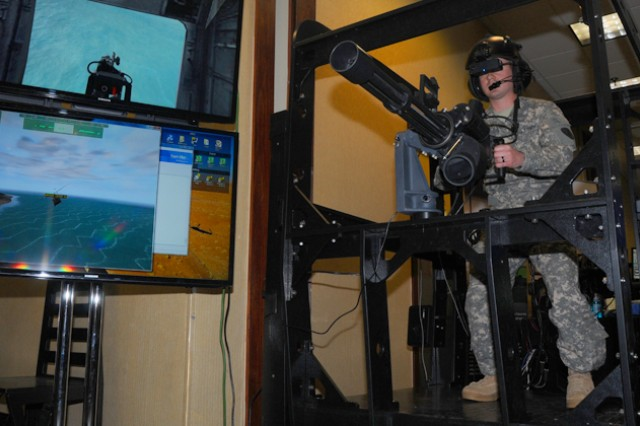W01 Elliot Worel, B Company, 1st Battalion, 145th Aviation Regiment, tests out a Complete Aircrew Training System-Mounted Arms Simulator during the Aviation Training Industry Day March 21 at The Landing.