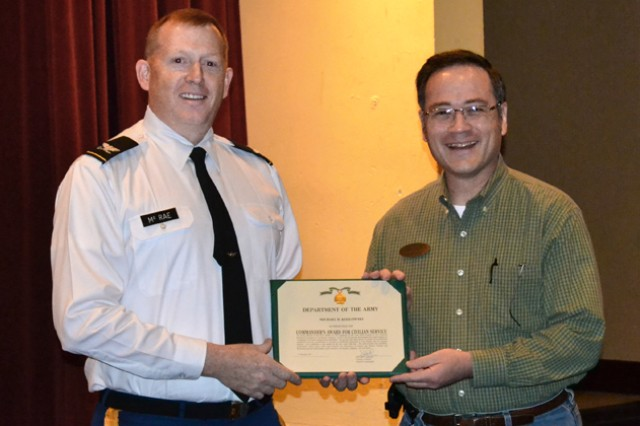 Mike Kozlowski, ACS personal finance readiness specialist, accepts the DFMWR Quality of Life Award from Col. Stuart J. McRae, Fort Rucker garrison commander, during a ceremony at The Landing.