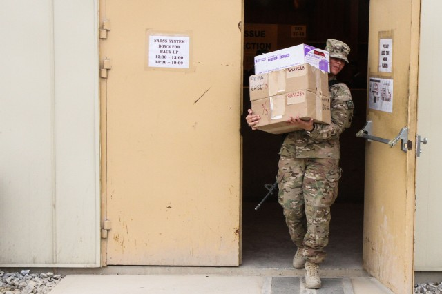 PARWAN PROVINCE, Afghanistan - Army Spc. Janet Pagan, a unit supply specialist assigned to the 72D Expeditionary Signal Battalion from Schweinfurt, Germany, leaves a storage facility with supplies for her unit at Bagram Airfield, Afghanistan, March 18, 2013. Pagan is tasked with supplying her unit with materials and parts while deployed and in garrison. (U.S. Army Photo by Spc. Brian Smith-Dutton TF 3/101 Public Affairs)
