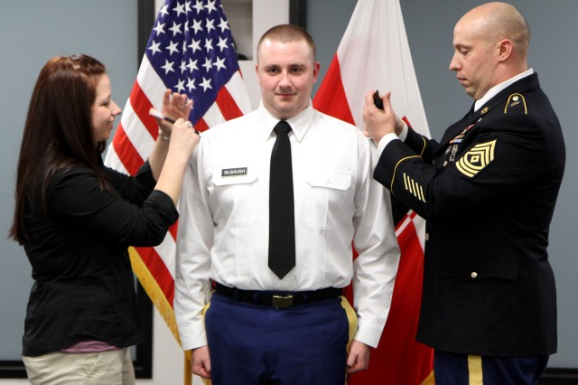 Newly promoted Staff Sgt. David Silbaugh, an administrative Soldier at First Army Division East, is pinned by his wife Lindsey Silbaugh, with the help of 1st Sgt. Joseph Smith, first sergeant, Headquarters, Headquarter Detachment, during his promotion ceremony.