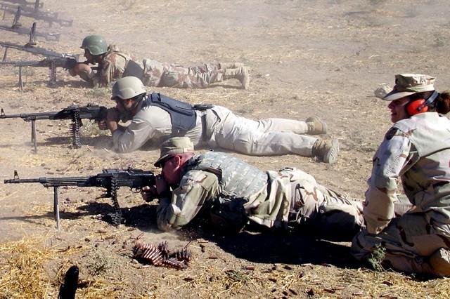 Capt. LeeAnn Roberts instructs Iraqi trainees and a coalition soldier on proper firing techniques at the Al Kasik Training Base firing range, Iraq, Jan. 30, 2006.