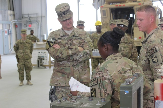 Pvt. Bianca Kelley explains the in processing of non-rolling stock to Sgt. Maj. of the Army Raymond Chandler. A unit does a layout of equipment, including the thumb screw de-install of Government Furnished Equipment (GFE) such as Blue Force Tracker, CROWS, CREW, Dukes, Boomerang.  Equipment is tagged for shipment and segregated.  It is then packed by shipping DODAAC for final destination. (Photo by Sharonda Pearson, 401st AFSB Public Affairs)