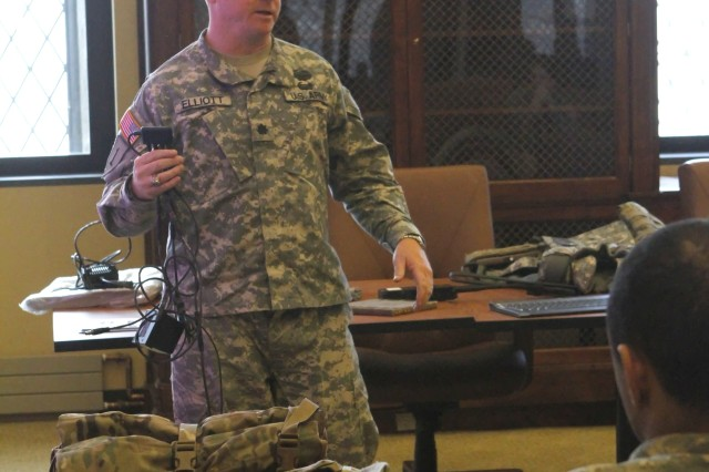 Lt. Col. Charles Elliott, the general chemistry course director in the Department of Chemistry and Life Science, at the U.S. Military Academy at West Point, N.Y., demonstrates the Soldier Worn Integrated Power Equipment Systems to a group of cadets during the Army Energy-Informed Culture Summit, March 27, 2013, at West Point. Part of the energy summit focused on the coordination of efforts for operational and installation energy awareness, education and training.