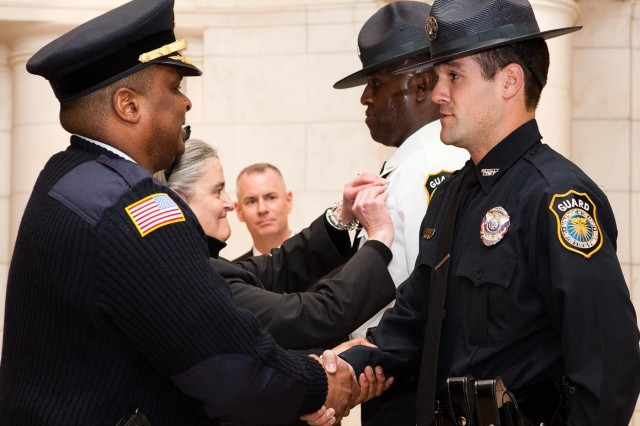 (From the left) Joint Base Myer-Henderson Hall Police Chief William Johnson and Arlington National Cemetery Executive Director Kathryn Condon pin the badges on Uniformed Public Safety Division Capt. Marieo Foster and UPSD Deputy Chief Lt. Daniel Feeman, during a badge ceremony at the Memorial Amphitheater Chapel March 27. (Photo by Rachel Larue)