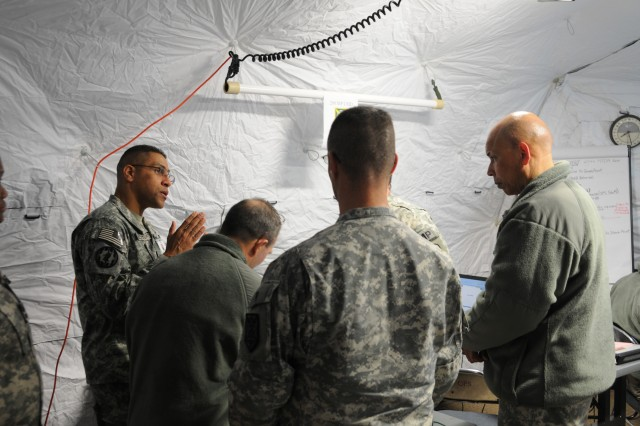 CAMP WALKER, Korea -- Army Reserve Col. Kevin Acosta (far left) talks with 200th Military Police Command staff during Exercise Key Resolve 13 Camp Walker, Korea. Acosta is the assistant chief of staff - operations officer for the 200th MPCOM. More than 40 Soldiers from the 200th MPCOM, headquartered at Fort Meade, Md., participated in the annual computer-simulated exercise. (Army Reserve photo by Staff Sgt. Lloyd Shellenberger)