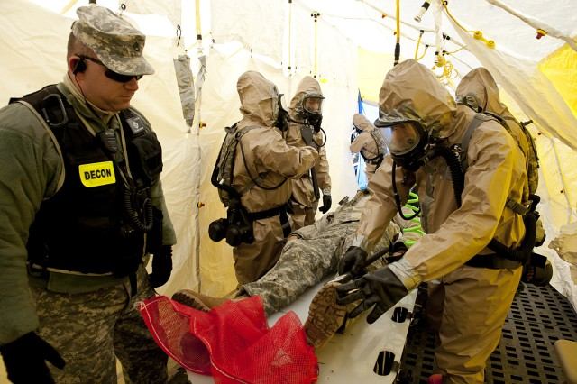 Members of the Kentucky Chemical, Biological, Radiological, Nuclear and High Yield Explosive Enhanced Response Force Package decontamination element decon a mock victim under the watchful eye of an observer/controller during training at Muscatatuck Urban Training Center in Butlerville, Ind., March 22, 2013.
