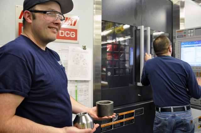 Arsenal machinist Joey Zwack (left), is holding a 81mm base cap that was just machined in less than 30 minutes. Meanwhile, Harvey Downs, Boldt Machinery Inc., is working through the programming on the new machine.