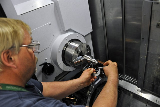 Twenty-year Arsenal machinist Tom Ostrander is checking the tolerances on the new high-tech machine.