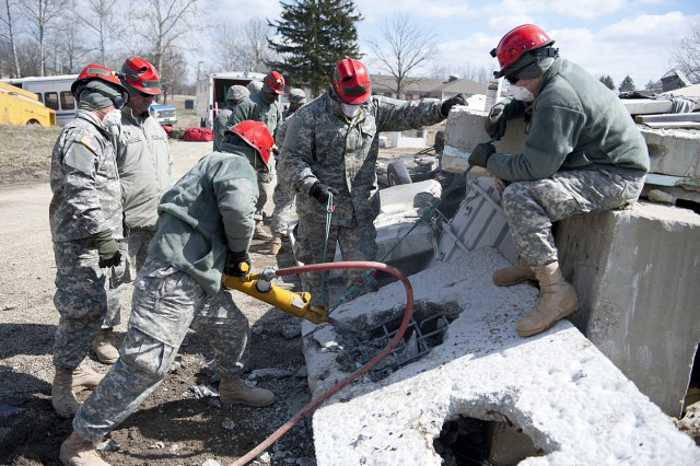 Members of the Kentucky Chemical, Biological, Radiological, Nuclear and High Yield Explosive Enhanced Response Force Package breaching and breaking team learn how to use a jackhammer safely to get through concrete in order to rescue a victim following a disaster during training at Muscatatuck Urban Training Center in Butlerville, Ind., March 22, 2013.