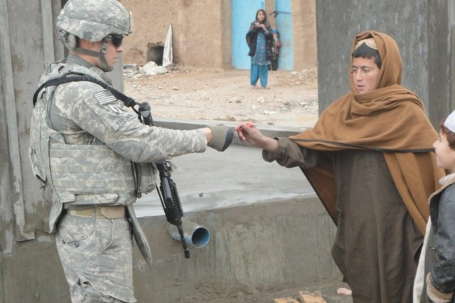 Capt. David Freeman provides a pen to a young Afghan boy while patrolling the area during his deployment to Kandahar in 2010. (Courtesy photo)