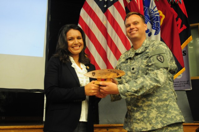Congresswoman Tulsi Gabbard receives a token of appreciation from Lt. Col. Todd Johnson, commander of the Headquarters and Headquarters Battalion, 25th Infantry Division, during the Women's History Month observance at the Tropics Warrior Zone, March 27, 2013 on Schofield Barracks, Hawaii. She was presented with the gift for her role as the guest speaker. The event was held to recognize and honor the contributions and accomplishments of female Soldiers past, present and future.