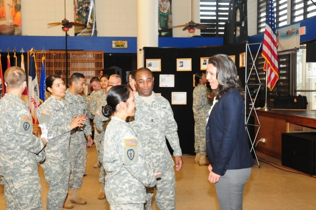 Congresswoman Tulsi Gabbard speaks to Capt. Sakura Creedon and 1st Sgt. Edward Gaston, command team of Signal Company, Headquarters and Headquarters Battalion, 25th Inf. Div. of her experiences as a politician and a Soldier in the Hawaii National Guard during the Women's History Month observance at the Tropics Warrior Zone, March 27, on Schofield Barracks, Hawaii. The event was held to recognize and honor the contributions and accomplishments of female Soldiers past, present and future.