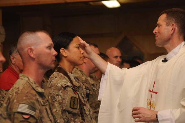 Navy Lt. Cmdr. Denise Whitfield (left) receives the Sacrament of Confirmation during a Baptism ceremony at mass services held on Kandahar Airfield, March 30, 2013. (U.S. Army photo by Sgt. Ashley Bell)