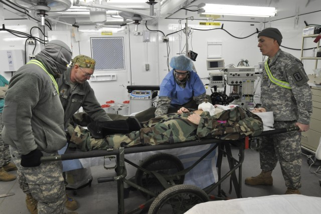 Soldiers with the 212th Combat Support Hospital prepare a simulated casualty for surgery in the operating room during a field training exercise at Miesau, Germany, March 15, 2013. The OR is one of two in the 64-bed field hospital which is constructed of dozens of tents and specially designed metal containers.