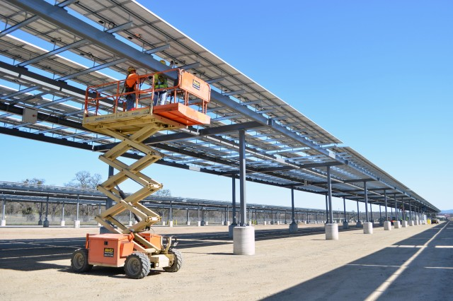 Construction workers complete electrical connections on phase 2 of a solar microgrid project at Fort Hunter Liggett, Calif., March 12, 2013. The U.S. Army Corps of Engineers Sacramento District managed construction of the project, awarding contracts of $8.4 million for phase I and $9.7 million for phase 2. Phase 2, scheduled for completion in May 2013, will generate one megawatt of power and is expected to be the second of four at the post. Phase 1 was completed in April 2012, and also generates one megawatt of power, enough energy to power 250 to 300 homes. Along with the energy production, the panel arrays form a canopy that will shade the majority of the post's vehicles. Fort Hunter Liggett is one of six pilot installations selected by the U.S. Army to be net zero energy, meaning the installation will create as much energy as it uses.