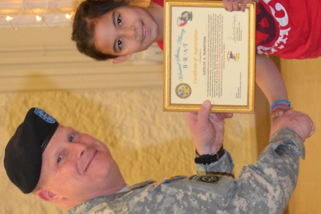 Brig. Gen. Duane Gamble, Army Sustainment Command deputy commanding general, presents Katelyn Robertson, daughter of retiree Maj. Christopher Robertson, with an Army BRAT certificate during the ASC quarterly Award, Retirement and Retreat Ceremony held in Rock Island Arsenal's Heritage Hall March 28.