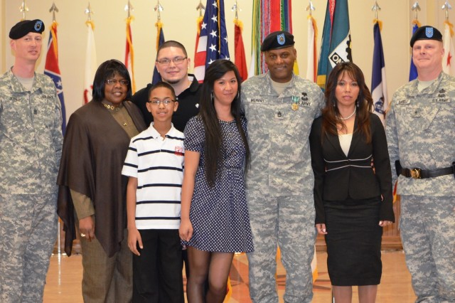 Retiree Sgt. 1st Class Ronald Wilmont and family members gather for a photo with Brig. Gen. Duane Gamble, Army Sustainment Command deputy commanding general, and Sgt. Maj. Keith Jones, Distribution Management Center, during the ASC quarterly Award, Retirement and Retreat Ceremony held in Rock Island Arsenal's Heritage Hall March 28.