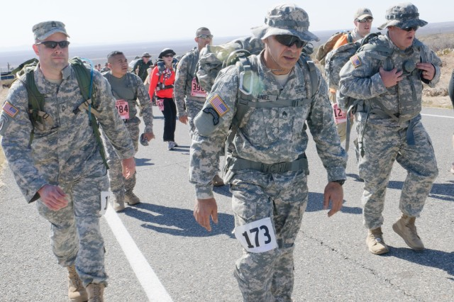 Sgt. 1st Class Mark Johns, Sgt. Erik Daniel and Spc. Kenneth King push through the effects of the high elevation as they make their way up the steep seven mile incline during the Bataan Memorial Death March. The course at White Sands Missile Range, N.M. starts at an elevation of 4,000 feet while the team's home station of Fort Gordon, Ga. is at an elevation of 160 feet.