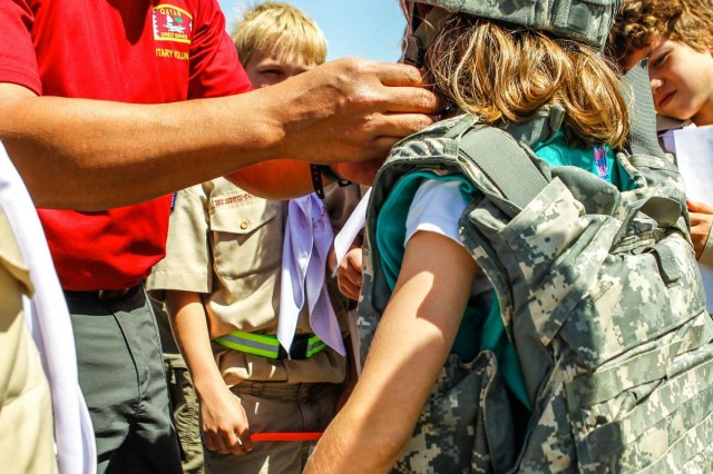 Joe Reyes helps a Girl Scout don U.S. Army armor. The Boy Scout Camporee on Camp As Sayliyah allowed the Girl Scout to join them during their activities all across Camp As Sayliyah. (U.S. Army photo by Jonald Lalas)