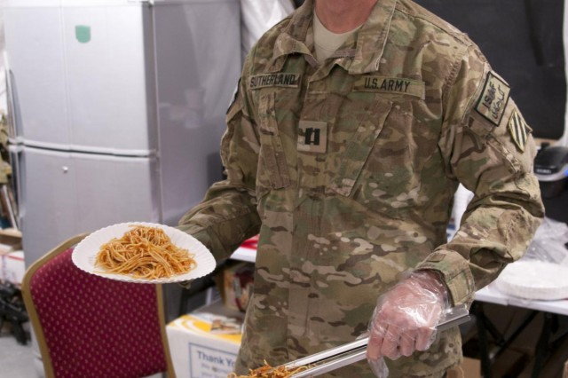 U.S. Army chaplain Capt. Arles Curtis Sutherland, Seventh-day Adventist chaplain for 1st Battalion, 41st Field Artillery Regiment, 1st Armored Brigade Combat Team, 3rd Infantry Division, Combined Task Force Raider, serves spaghetti at his bi-weekly pasta prayer dinner at Forward Operating Base Apache, on March 27, 2013. (U.S. Army Photo by Spc. Jovi Prevot)