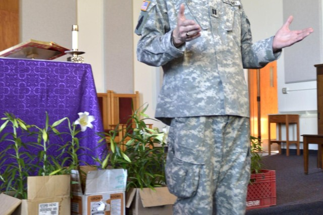U.S. Army Capt. Barry C. Malone, acting rear detachment chaplain for 555th Engineer Brigade, receives the first delivery of Easter lilies from Soldiers with the Northwest Joint Regional Correctional Facility, at the Evergreen Chapel on Joint Base Lewis-McChord, Wash., March 22, 2013.  (U.S. Army photo by Sgt. Adam Keith/Released)