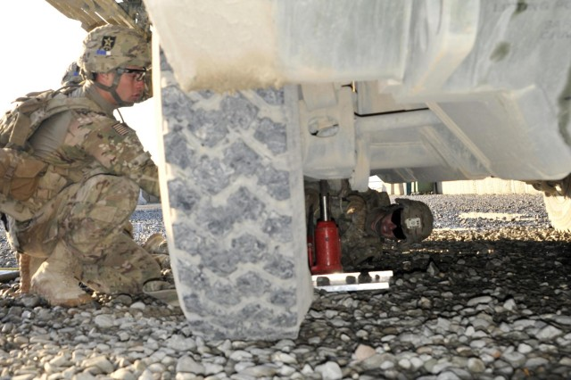 U.S. Soldiers with Charlie Company, 2nd Battalion, 23rd Infantry Regiment change a tire on a Stryker armored vehicle during the Top Tomahawk competition at Forward Operating Base Spin Boldak in Kandahar province, Afghanistan, March 29, 2013. The competition tested the Soldiers' physical endurance, marksmanship skills, and technical and tactical proficiency. (U.S. Army photo by Staff Sgt. Shane Hamann/Released)