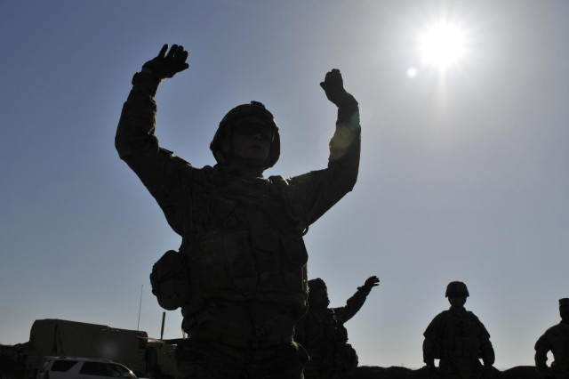 U.S. Soldiers with Charlie Company, 2nd Battalion, 23rd Infantry Regiment are silhouetted against the sun as they exercise before testing marksmanship skills during the Top Tomahawk competition's stress shoot event at Forward Operating Base Spin Boldak in Kandahar province, Afghanistan, March 29, 2013. The competition tested the Soldiers' physical endurance, marksmanship skills, and technical and tactical proficiency.  (U.S. Army photo by Staff Sgt. Shane Hamann/Released)