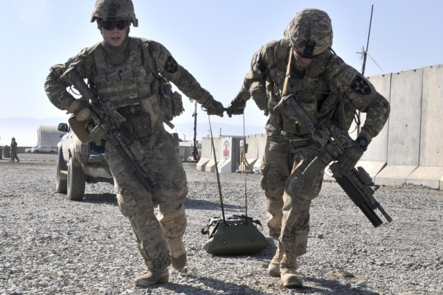 U.S. Army Spc. Matthew Brew, left, and Spc Kirk Calabrese, both with Bravo Company, 2nd Battalion, 23rd Infantry Regiment, drag a litter packed with sandbags simulating a casualty during the Top Tomahawk competition at Forward Operating Base Spin Boldak in Kandahar province, Afghanistan, March 29, 2013. The competition tested the soldiers' physical endurance, marksmanship skills, and technical and tactical proficiency.  (U.S. Army photo by Staff Sgt. Shane Hamann/Released)