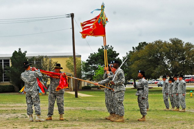 "Lt. Col. Richard Ng (far left), Tampa, Fla. native and commander of the 1st ""Dragon"" Battalion, 82nd Field Artillery Regiment, 1st ""Ironhorse"" Brigade Combat Team, 1st Cavalry Division and Command Sgt. Maj. Steven Rosales (second from left), the command sergeant major for the Dragon Battalion and Fresno, Calif. native, attach award streamers to the Dragon colors at an award ceremony March 28 at Fort Hood, Texas. The Dragon Battalion received the Meritorious Unit Commendation for ""exceptionally meritorious achievements"" during Operation New Dawn and the Army Superior Unit Award ""for outstanding meritorious service and outstanding performance"" while stationed at Fort Hood, according to the award citations given by the Army."