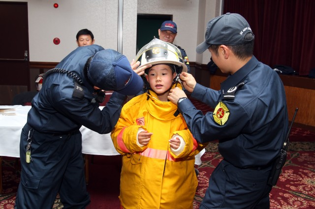 Camp Zama's Fire Department help children of Garrison Japan employees try on fire-proof suits after a fire safety demonstration at the Zama Community Club, April 2 during the 2nd annual 'Bring your children to work day' event. (U.S. Army photo by Candateshia Pafford)