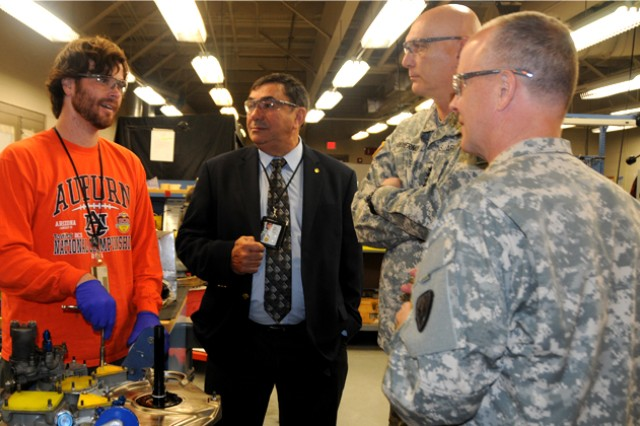 Robby Cain, Cairns Army Airfield engine shop employee, speaks with Army Chief of Staff Gen. Raymond T. Odierno about his job and his training during the chief of staff's visit to the airfield.