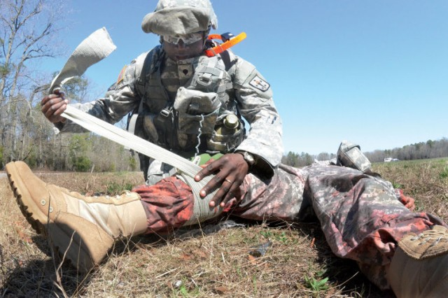 Spc. Justin Essah, representing the Soldier Support Institute at Fort Jackson, S.C., applies bandage to the leg of a simulated casualty during CASCOM's Ultimate Warrior Competition April 2.  The Soldier skills event, held April 1-3, brought together 13 Soldiers who represented subordinate elements in the categories of Soldier, noncommissioned Officer, instructor, retention NCO and advanced individual training platoon sergeant of the year competitions.