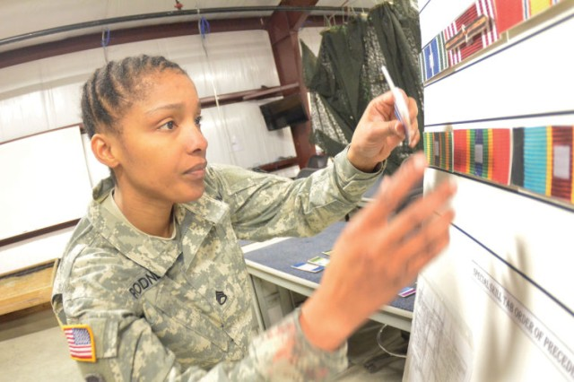 Staff Sgt. Petagail Rodney, an Instructor of the Year competitor, arranges mock ribbons and awards during the Ulitimate Warrior Mystery Event April 2 at the Fort Lee range complex classroom.