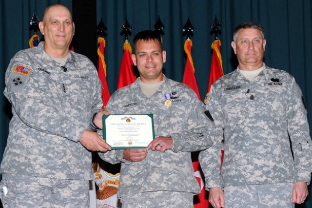 CW3 Ronald Sandler, 1st Bn., 212th AVN, stands with Gen. Raymond T. Odierno, Army chief of staff, and Sgt. Maj. of the Army Raymond F. Chandler III, after Odierno presented him with the Soldiers Medal during a town hall at Fort Rucker April 1.