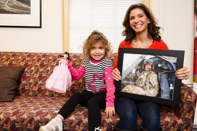 Layla, 4, sits next to her mother Antonette Hornsby holding a photograph of her husband Chief Warrant Officer 3 Brian Hornsby, in the Survivor Outreach Services office in Bldg. 203, on Joint Base Myer-Henderson Hall, Va., March 29, 2013. Brian Hornsby was killed in a helicopter crash last year. (Joint Base Myer-Henderson Hall PAO photo by Rachel Larue)